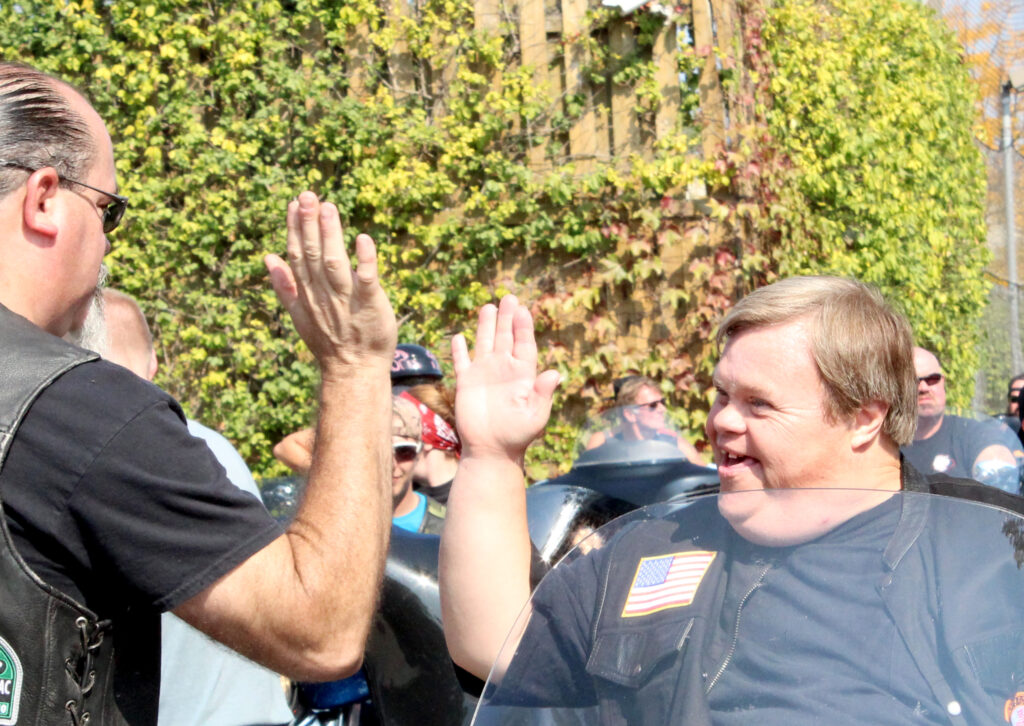 Ricky giving a high five to one of the motorcycle riders at Ricky's Ride event.