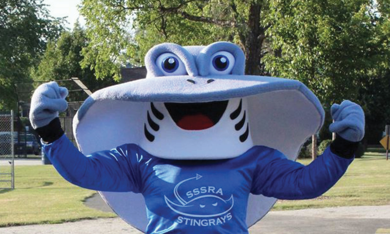 Sammy Stingray mascot poses for a picture in a park.