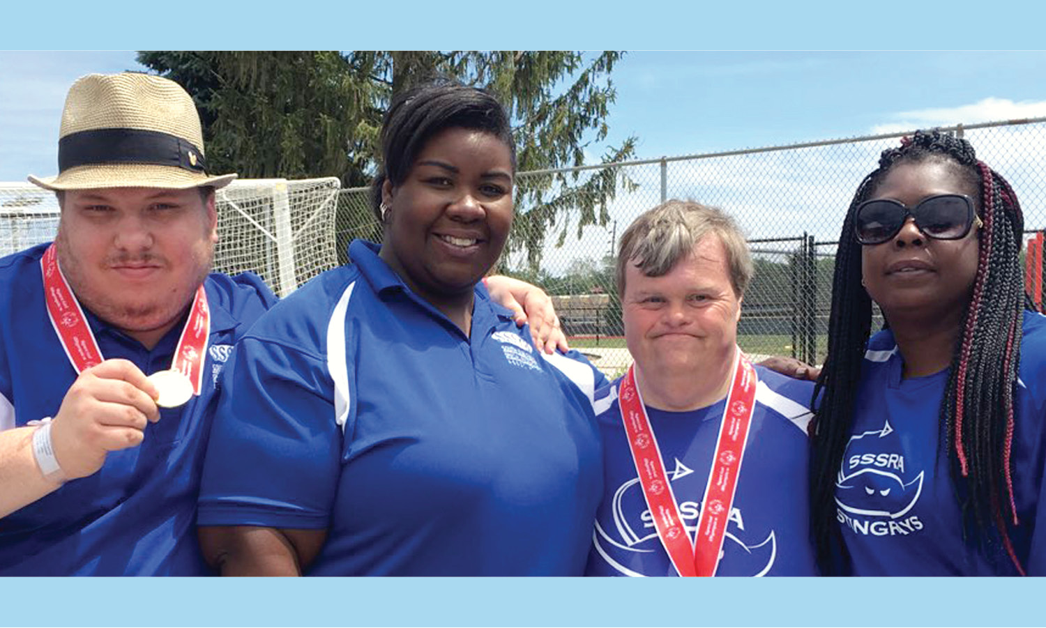 2 Special Olympics athletes and 2 Special Olympics coaches. The athletes are wearing medals.