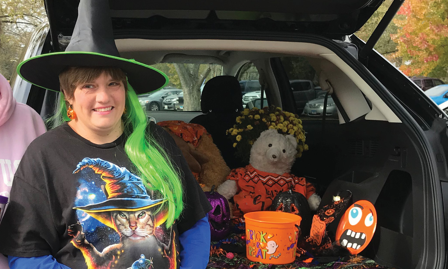 Woman wearing a witch hat, posing in front of her trunk that is decorated for Halloween.